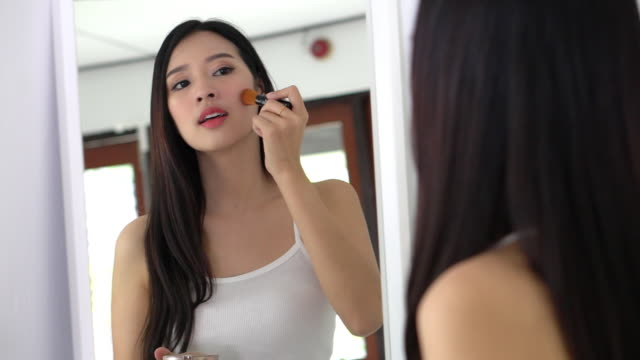beauty portrait asian woman applying makeup with brush of cheek look at mirror indoors, beautiful girl holding blusher, skincare and cosmetic concept, slow motion. - blusher make up stock videos and b-roll footage