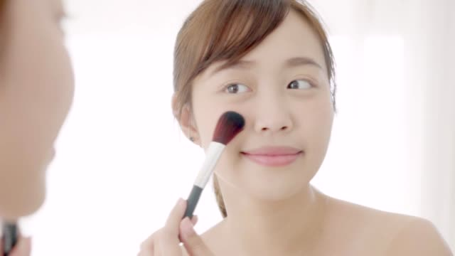 beauty portrait young asian woman smile with face looking mirror applying makeup with brush of cheek in the bedroom, beautiful asia girl healthy holding blusher, skin care and cosmetic concept. - blusher make up stock videos and b-roll footage