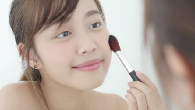 beauty portrait young asian woman smile with face looking mirror applying makeup with brush of cheek in the bedroom, beautiful of girl holding blusher, skin care and cosmetic concept. - blusher make up stock videos and b-roll footage