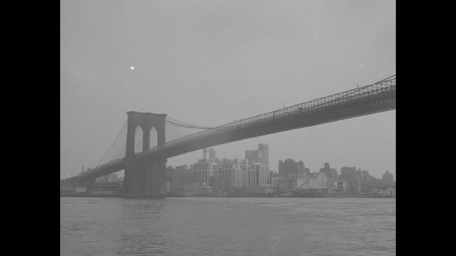 beauty shot brooklyn bridge over the east river in new york city / brooklyn street scene / people seated on curb of wide street, with pigeons in... - brooklyn bridge stock videos & royalty-free footage
