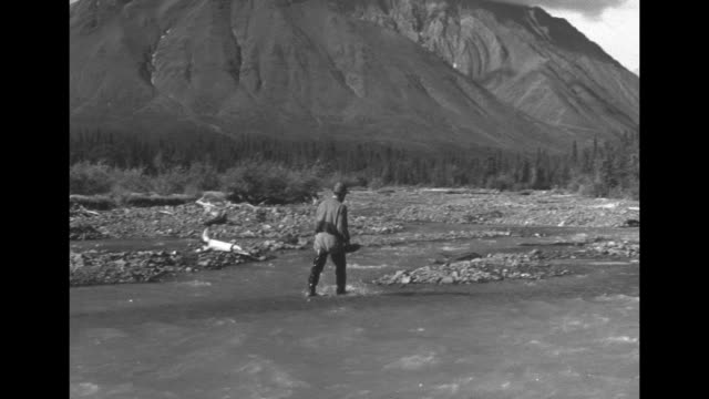 Beauty shot of rippling creek w cabin trees and snowcapped mt in BG / prospector walking in creek w pan mt in BG / man standing in creek panning for...