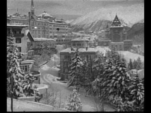 stockvideo's en b-roll-footage met beauty shots st. moritz, switzerland, site of 1948 winter olympics, with snow-covered trees, buildings, mountains in background and horse pulling... - werkdier