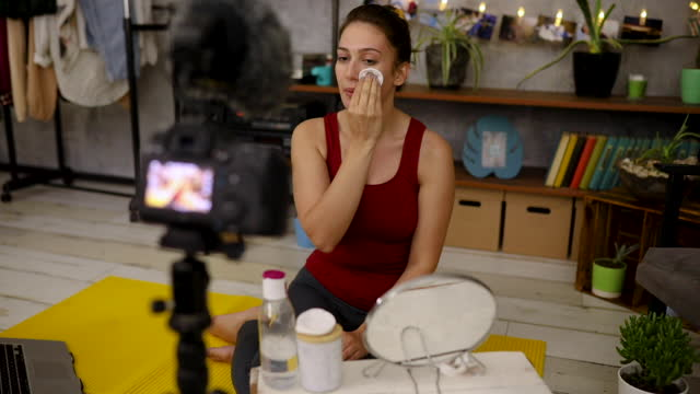 beauty vlogger using tonic water and cotton pad to remove her make up while filming tutorial about skin care - tonic water stock videos & royalty-free footage
