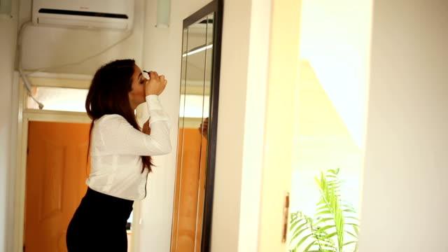 Schoonheid vrouw toepassing van make-up. Mooi meisje in de spiegel kijken en cosmetische met een grote borstel toe te passen. Meisje krijgt een blos op de jukbeenderen. Poeder, rouge