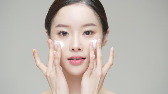 beauty - young woman putting face cream on her face in studio / south korea - east asian ethnicity stock videos & royalty-free footage