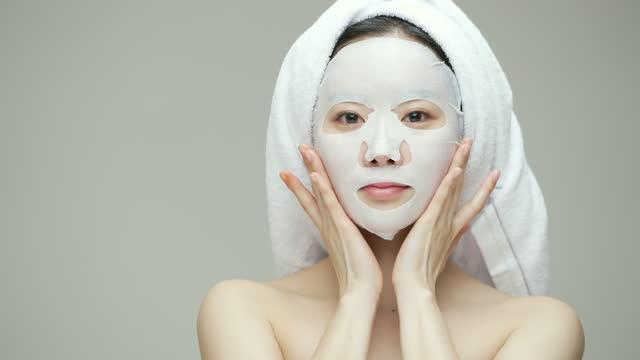 beauty - young woman putting on sheet mask in studio / south korea - koreanskt ursprung bildbanksvideor och videomaterial från bakom kulisserna