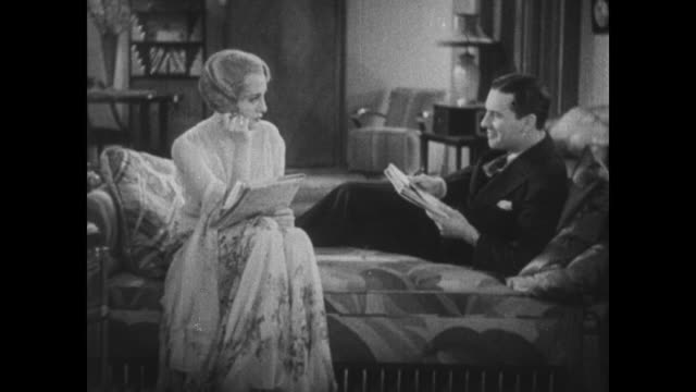1931 bebe daniels and ben lyon talk lovingly as they do crossword puzzle at home - crossword stock videos and b-roll footage