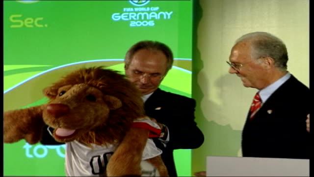London Franz Beckenbauer handing Sven Goran Eriksson a cuddly lion wearing a football shirt as Eriksson pulls the shirt down over lion's bottom