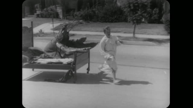 vídeos de stock e filmes b-roll de 1928 bed riding lobster chases nightgowned man down street - 1928