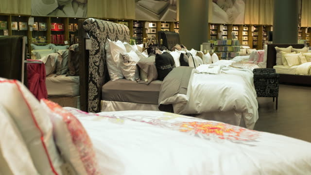 bedding and pillows displayed in furniture store - bedclothes stock videos & royalty-free footage