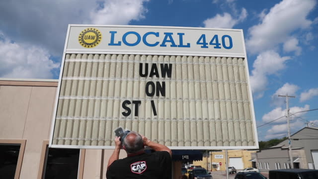vídeos de stock e filmes b-roll de united auto workers local 440 president kevin hutchinson puts the letters spelling uaw on strike on a marquee outside the local headquarters after... - general motors