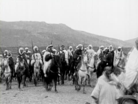1934 b/w montage ms cu ws bedouin armed men with rifles riding horses with atlas mountains in background, portrait of young tribesman standing against wall / rabat, morocco - ベドウィン族点の映像素材/bロール