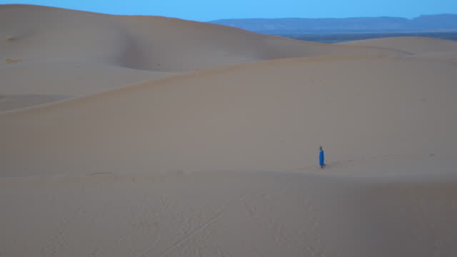 bedouin berber in blue clothes walking among the sand dunes of erg chebbi, saharan morocco  early in the morning - moroccan culture stock videos & royalty-free footage