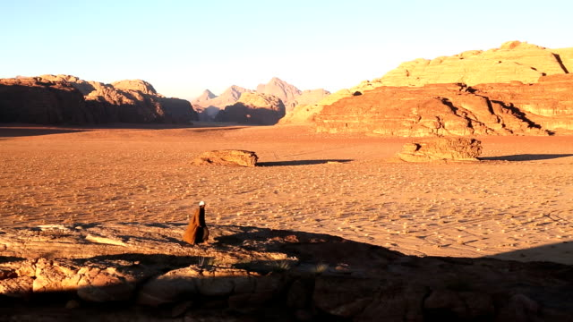 bedouin male walking in desert expanse wadi rum, jordan,  - 手をかざす点の映像素材/bロール