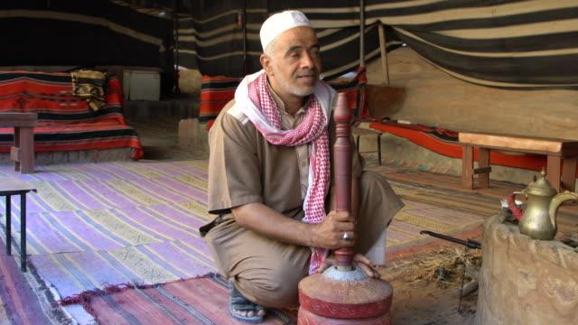 vídeos de stock e filmes b-roll de a bedouin man wearing traditional clothing explaining the use of an old wooden device for preparing coffee in wadi rum desert, jordan - chaleira de chá