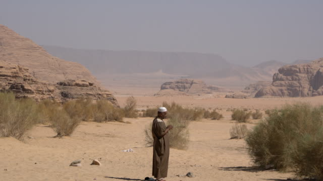 a bedouin man wearing traditional clothing praying alone in wadi rum desert, jordan - islam stock videos & royalty-free footage