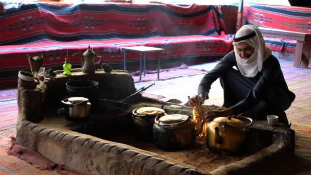 A Bedouin man wearing traditional clothing preparing tee in a Bedouin camp in Wadi Rum Desert, Jordan
