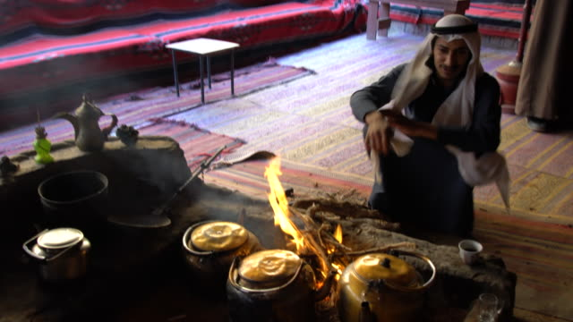 vídeos de stock e filmes b-roll de a bedouin man wearing traditional clothing preparing tee in a bedouin camp in wadi rum desert, jordan - chaleira de chá