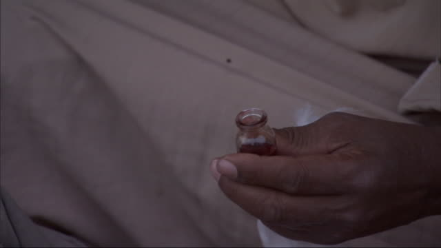 a bedouin practitioner pours and spreads a liquid on a patient's stomach. - vorbereitung stock-videos und b-roll-filmmaterial