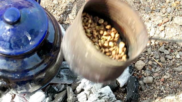 vídeos de stock, filmes e b-roll de povos do deserto beduíno torrefação de grãos de café sobre um fogo para preparar o café de estilo beduíno, de reunião do egito em wadi al gimal - egito