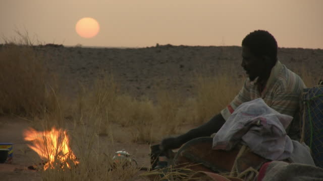 ms bedouin sitting by camp fire in sahara desert, sunset in background / zouerat, tiris zemmour, mauritania - モーリタニア点の映像素材/bロール
