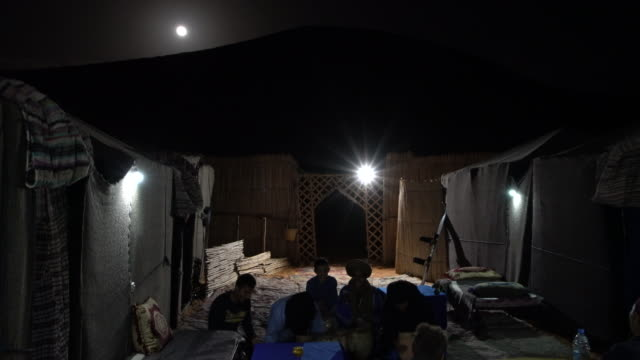 Bedouins singing and playing local berber music in a tourist camp at the dunes of Erg Chebbi in the evening, Saharan Morocco