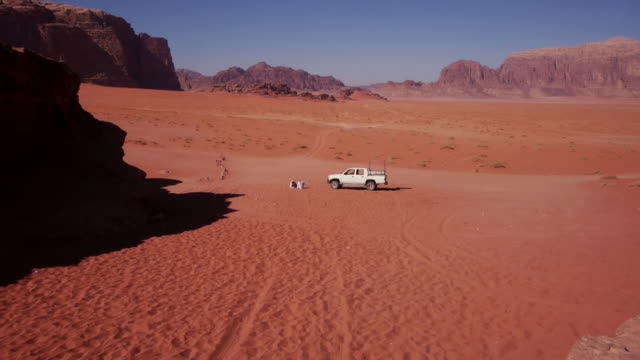 Bedouins sitting in sand next to their Jeep in Wadi Rum desert, Jordan, Middle East