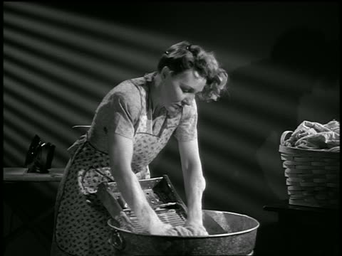 b/w 1947 bedraggled housewife doing laundry in washtub on washboard / industrial - washboard stock videos and b-roll footage