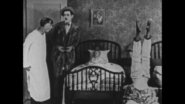 1925 bedraggled man forces doctor in nightshirt to examine hungry baby - 1925 stock videos & royalty-free footage