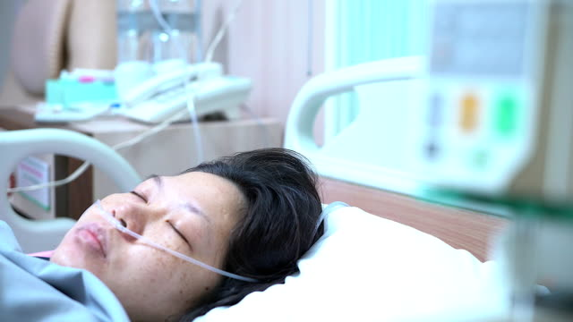 bedridden female patient lying in hospital bed, receive infusion while recovering from surgery. - respiratory equipment stock videos & royalty-free footage