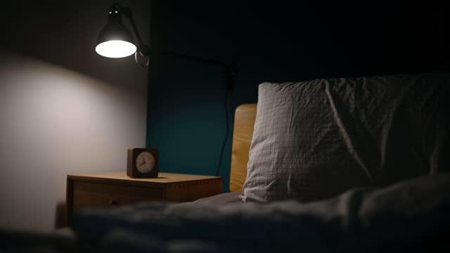 vídeos de stock, filmes e b-roll de quarto à noite iluminado por lâmpada elétrica com relógio na mesa noturna ao lado da cama com parede azul - electric lamp