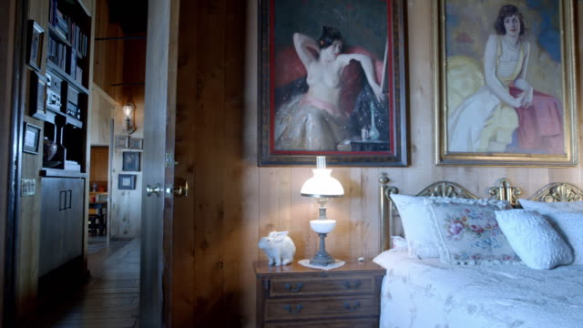 TS bedroom in rustic mountain lodge with 20th century American art hung on wood-paneled walls