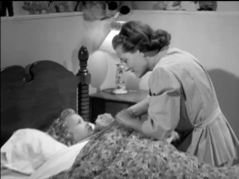 / bedroom interior showing mother tucking little girl into bed kissing her goodnight mother kisses little girl goodnight on january 01 1948 in ottawa - schlafenszeit stock-videos und b-roll-filmmaterial