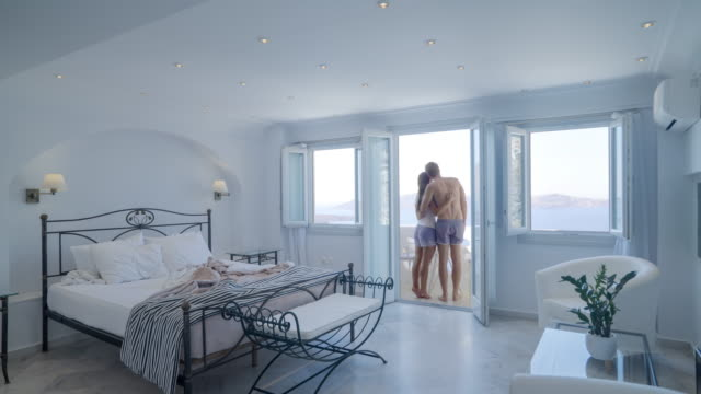 bedroom morning couple looking out of window - honeymoon stock videos & royalty-free footage