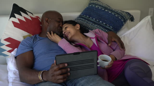 bedroom relax mixed race couple on bed using laptop computer e-commerce - mature couple stock videos & royalty-free footage