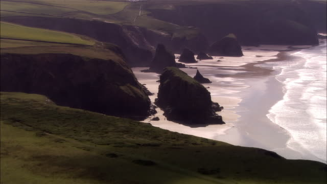 low aerial, bedruthan steps, cornwall, england - cliff stock videos & royalty-free footage