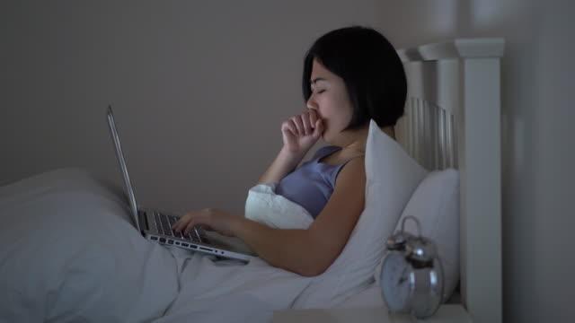 就寝前のラップトップあくび女性。 - 忙しい点の映像素材/bロール