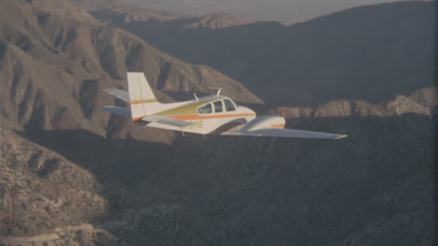 a-a beech baron twin l-r over mountains - プロペラ機点の映像素材/bロール