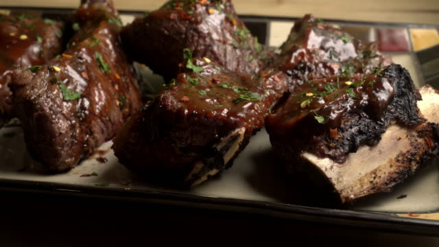 vídeos de stock, filmes e b-roll de sem osso e carne de costeletas com molho de churrasco numa bandeja rústica - bbq sauce