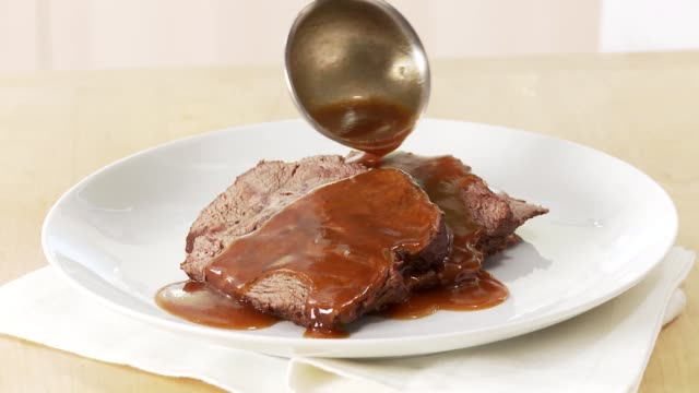 beef pot roast being served with gravy - roast beef stock videos & royalty-free footage