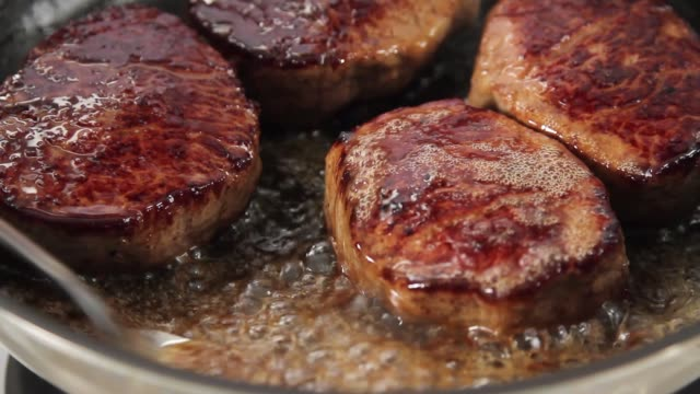 beef steaks being fried and poured with butter - steak stock videos & royalty-free footage