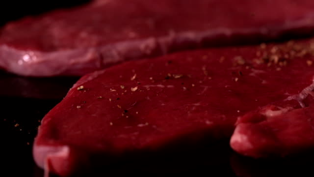 beef steaks on black surface being seasoned - steak stock videos & royalty-free footage