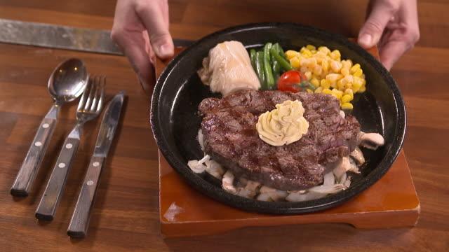 a beef tenderloin steak with green bean garnish on the pan - green bean stock videos & royalty-free footage