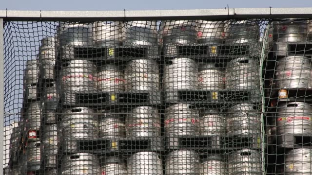 beer barrels sit stacked on pallets outside the stella artois lager beer brewery operated by anheuserbusch inbev nv in leuven belgium on saturday... - anheuser busch inbev stock videos and b-roll footage