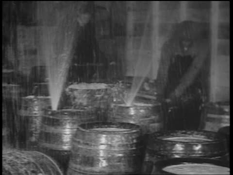 pan beer barrels spraying up fountains of beer / man smashing barrels / chicago - anno 1932 video stock e b–roll