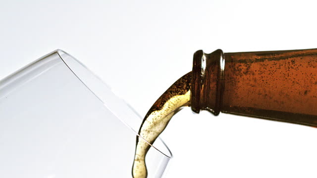 beer being poured into glass against white background, slow motion - wine glass stock videos and b-roll footage