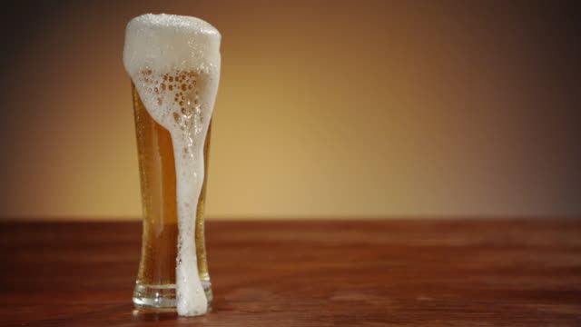 beer being poured into glass and overflowing gently - lager stock videos & royalty-free footage