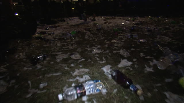 beer bottles and other trash litter the ground after a festival. - littering stock videos & royalty-free footage