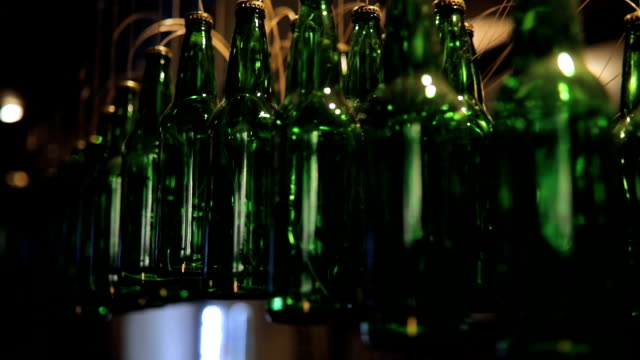beer bottles hanging in a row in bar - beer bottle stock videos and b-roll footage