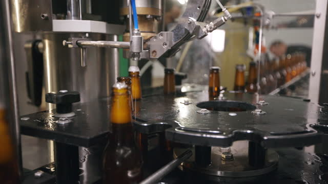beer bottles on automated machine during capping process - machinery stock videos & royalty-free footage